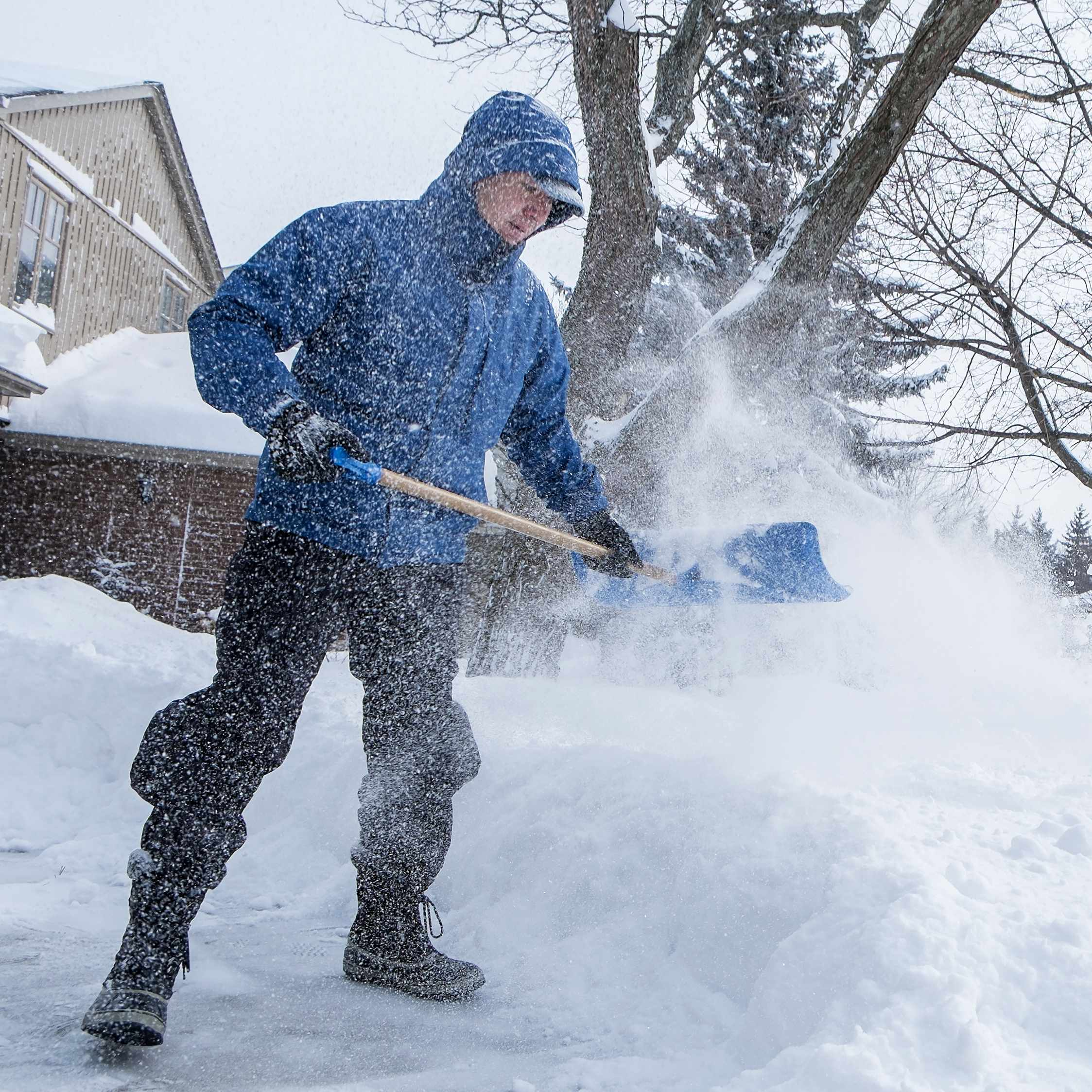 man shoveling snow from sidewalk after storm