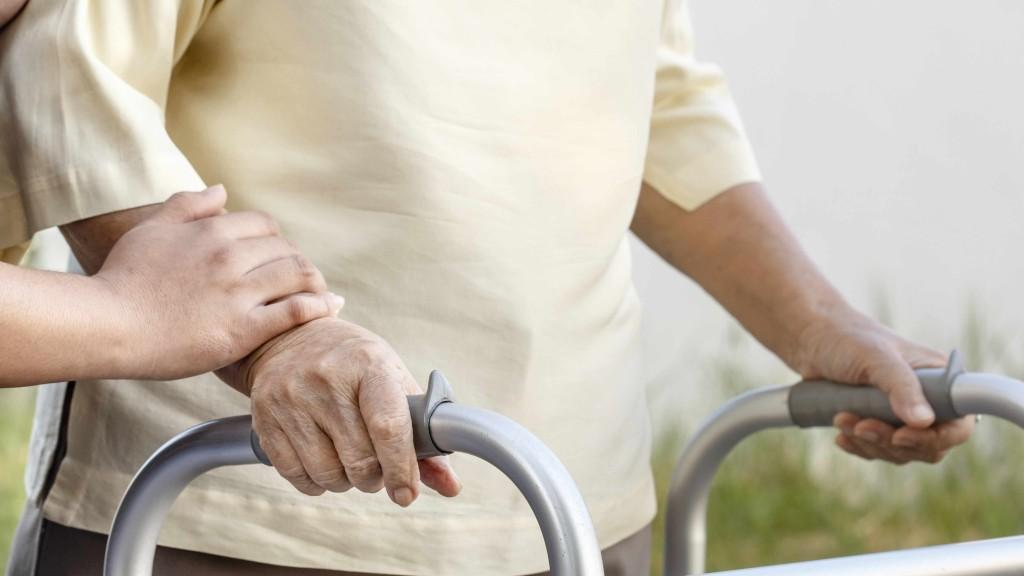 Mujer anciana y frágil que camina con un andador. 16x9