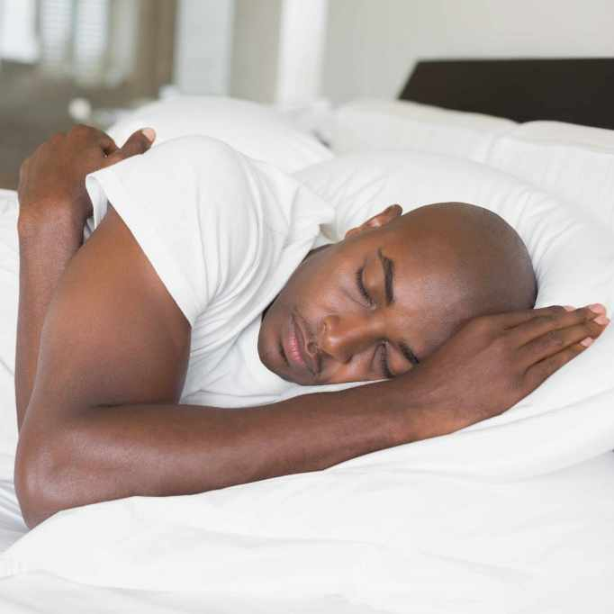 peaceful man sleeping in bed at home