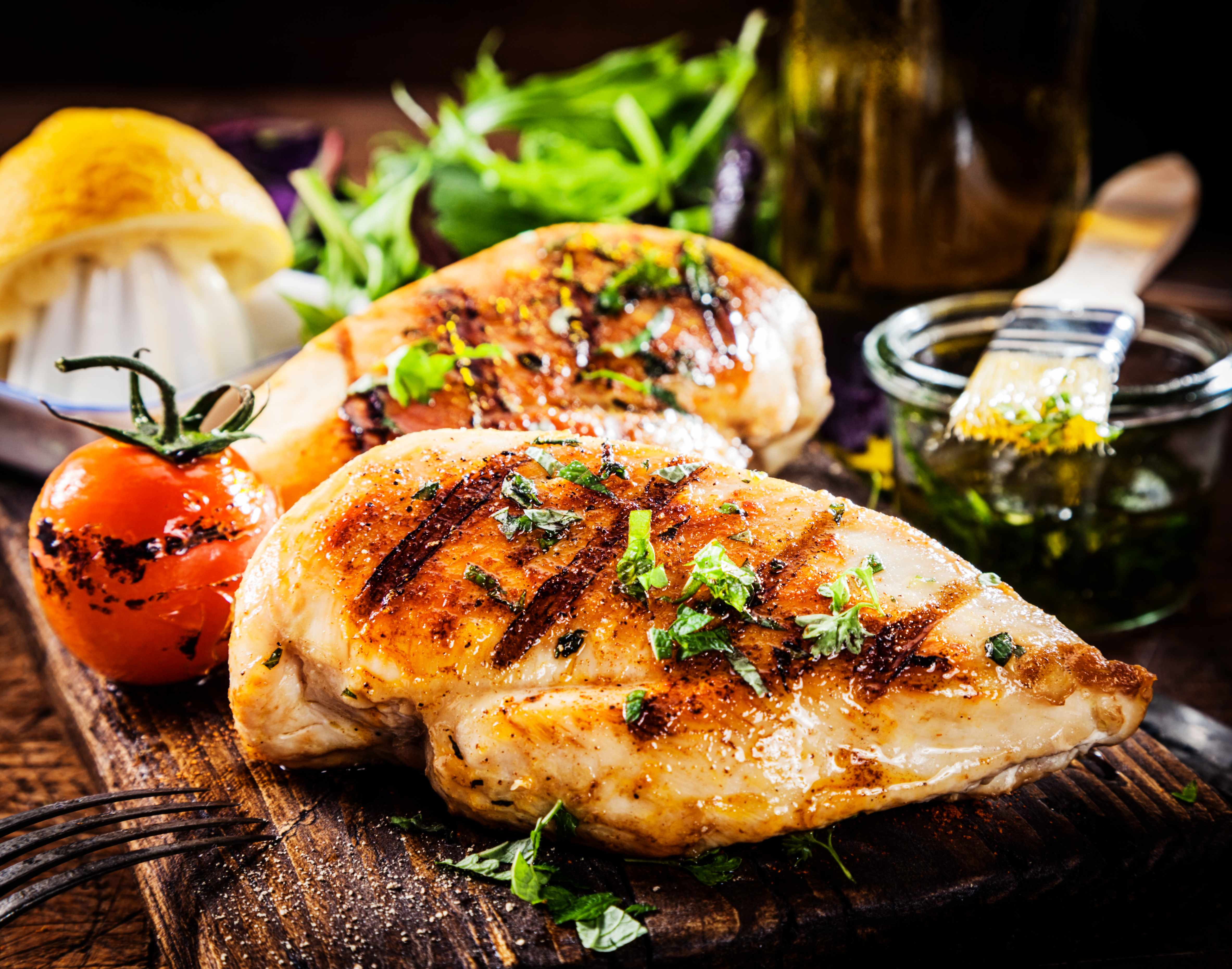 grilled chicken on cutting board with spices and vegetables