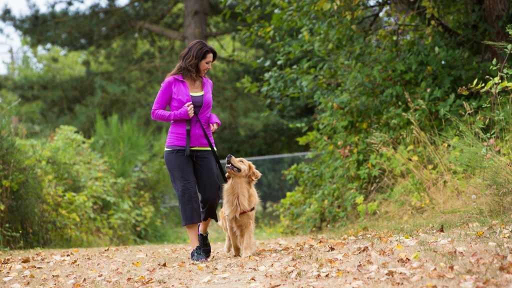 Una mujer hace ejercicio al caminar afuera con su perro