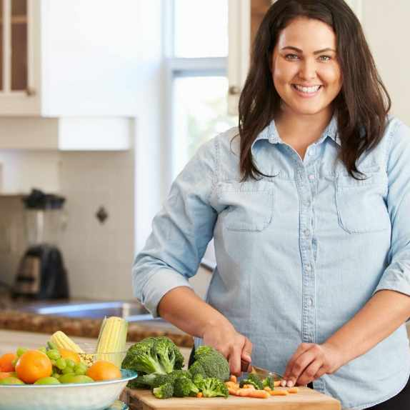 woman cutting food in kitchen