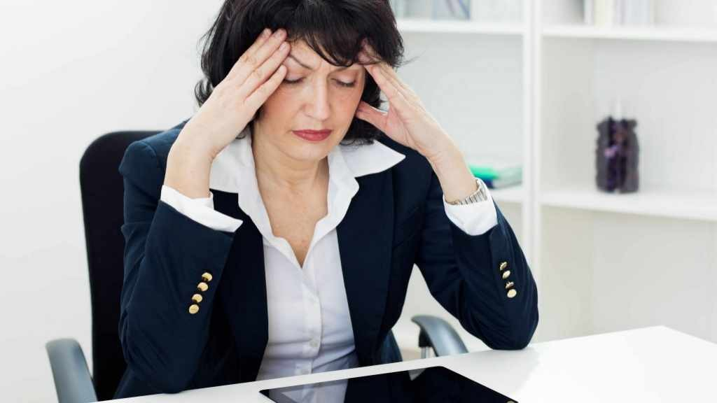 middle aged business woman at desk with tension headache, migraines, illness, stress, menopause