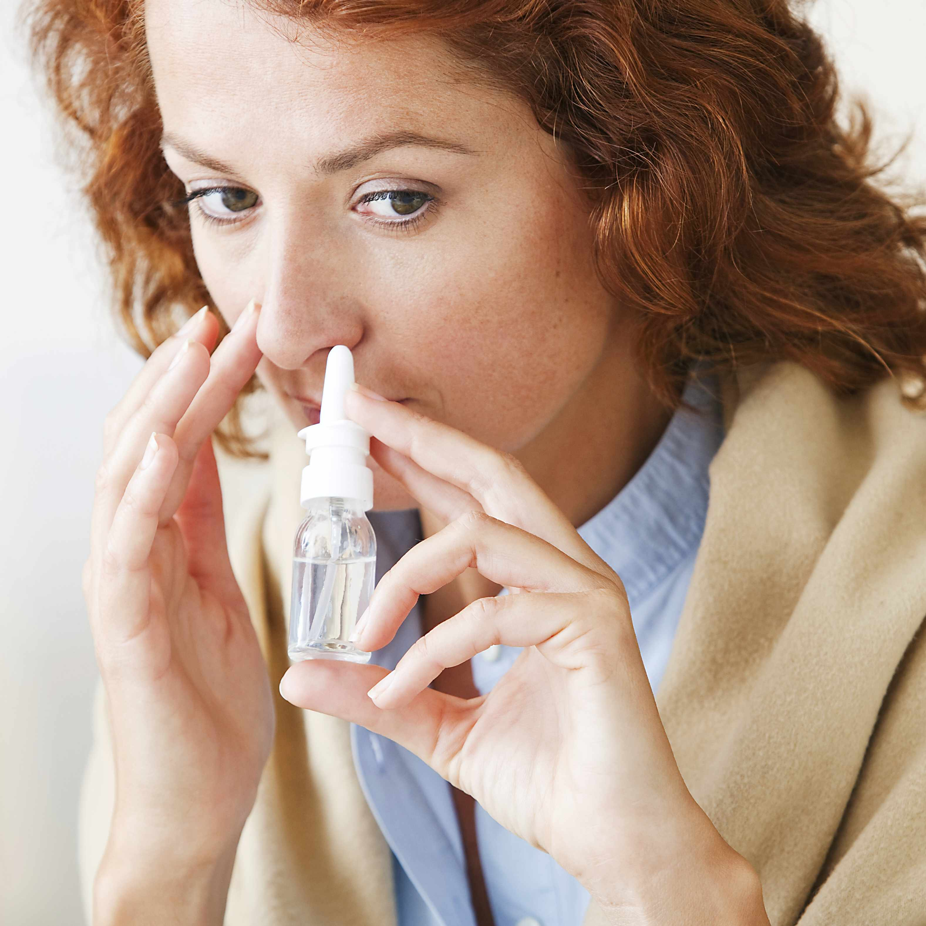 woman using decongestant nasal spray