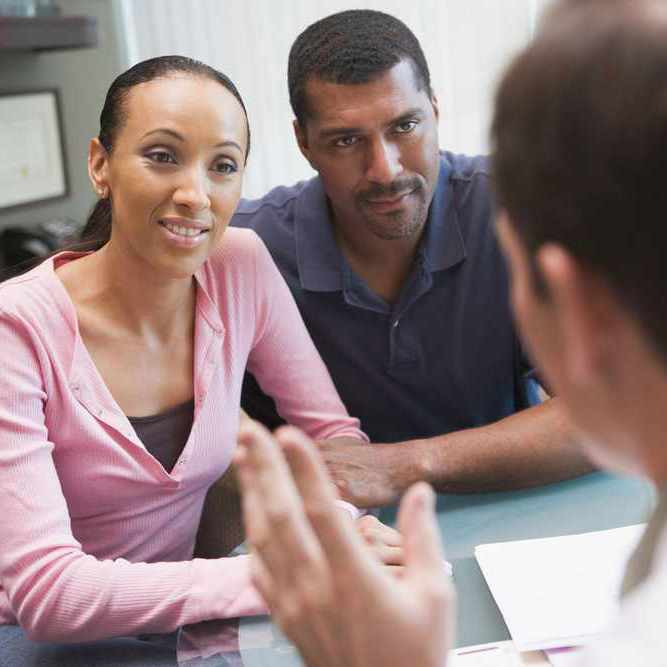 a young couple talking with a health care professional in his office