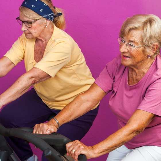 Portrait of two Elderly women doing leg exercises on stationary bikes in gym