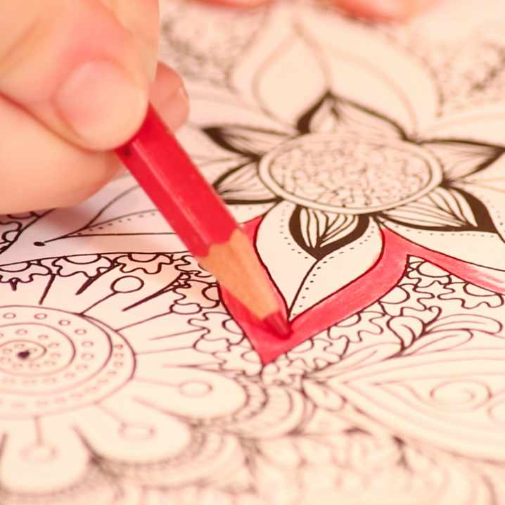 person coloring an image with red pencil
