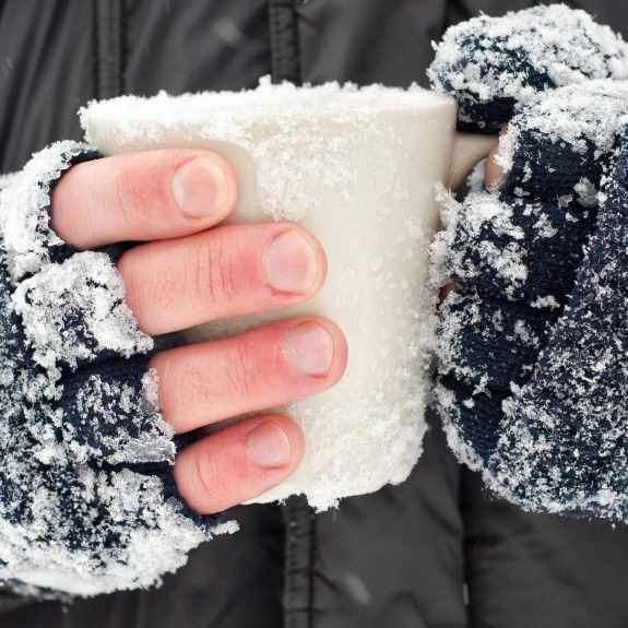 closeup of frozen hands covered in snow holding a cup, frostbite