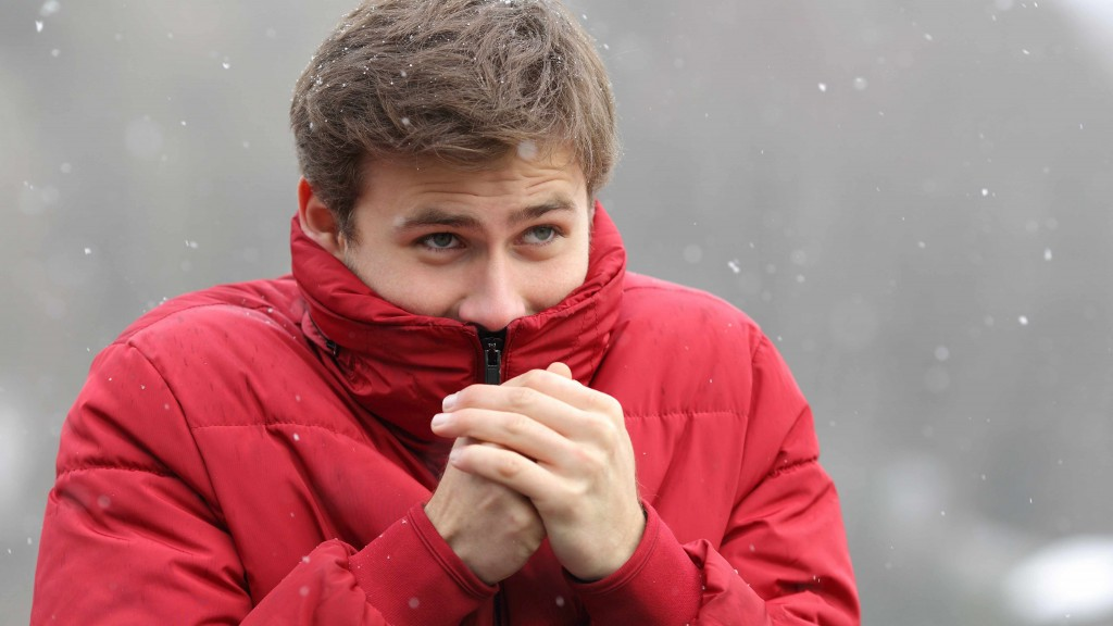 man outside in winter coat and snow, rubbing hands to keep warm, cold, dry skin