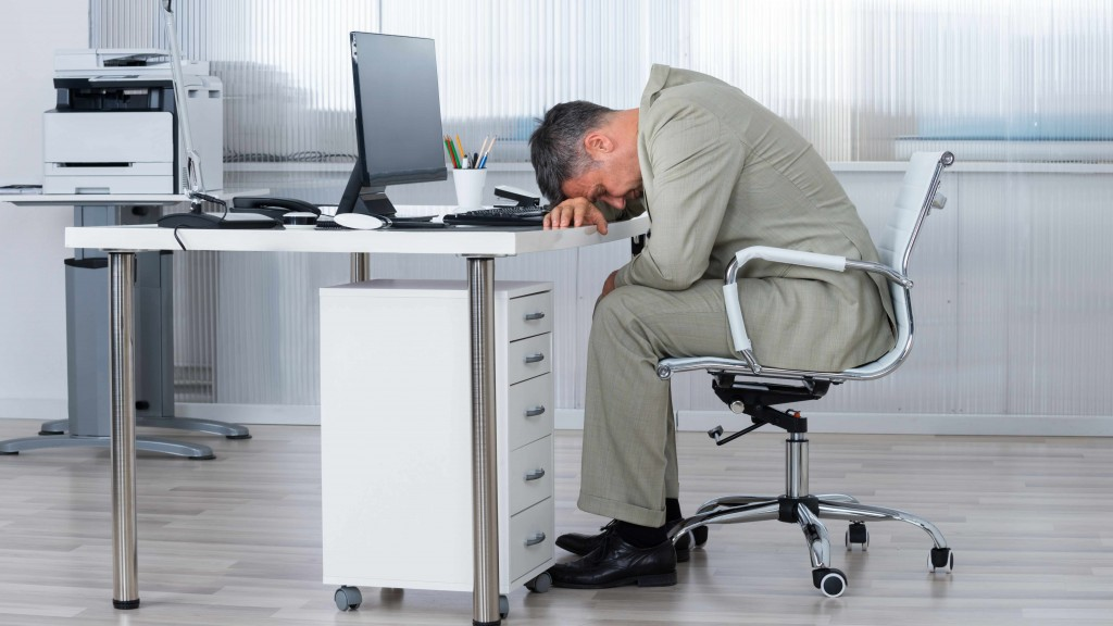 man sitting at office desk, slumped over computer asleep