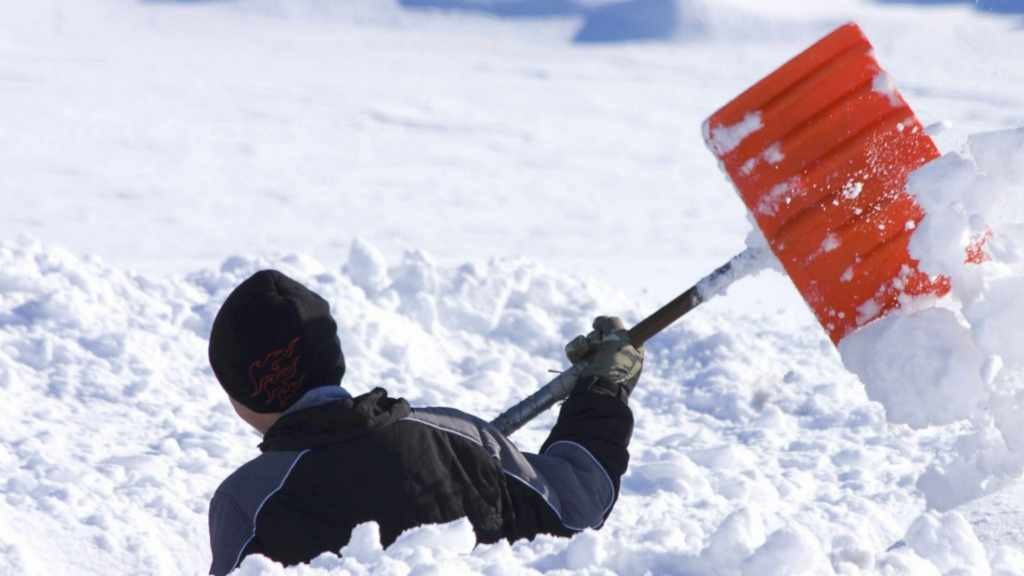person in waist deep snow shoveling
