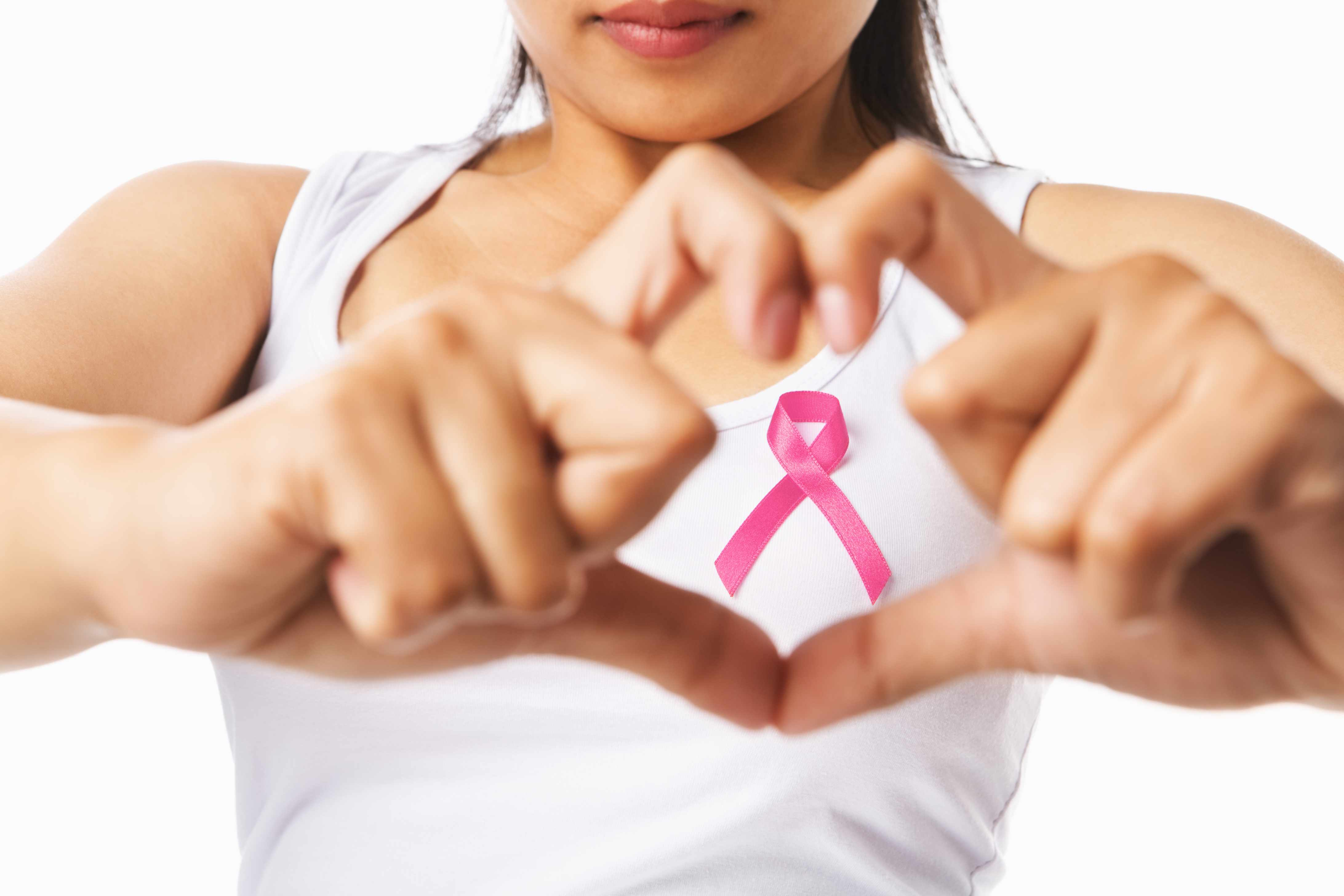 woman in tshirt making heart symbol with hands and pink ribbon, representing breast health