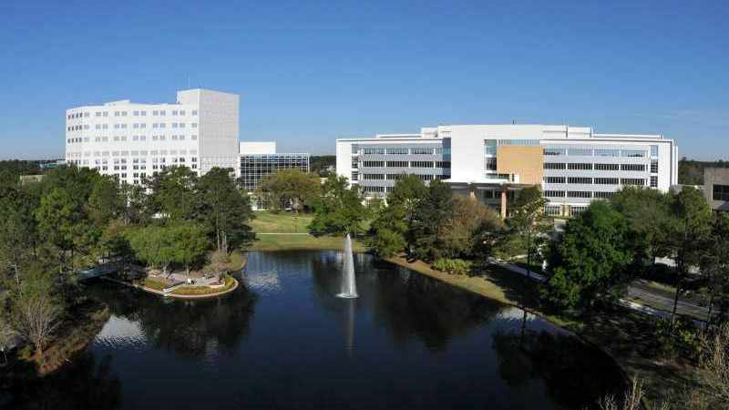 wide shot of Mayo Clinic Florida campus with blue sky and water in foreground