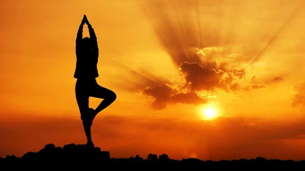 woman doing yoga, outdoors at sunset