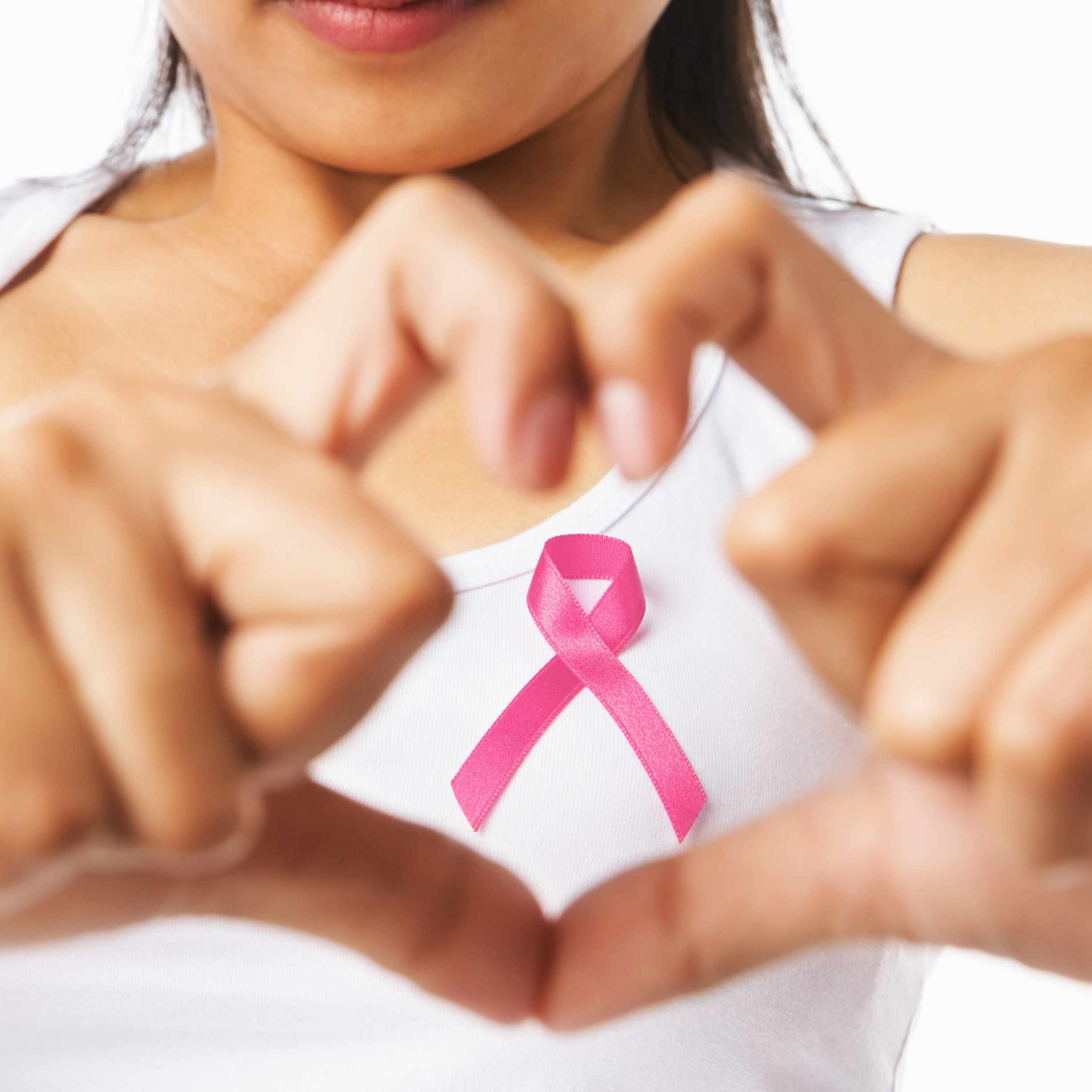 woman in t-shirt making heart symbol with hands and pink ribbon, representing breast health