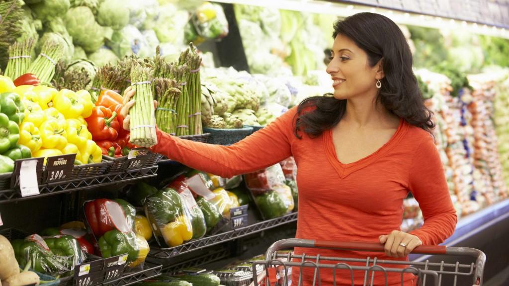 Una mujer compra comida sana y verduras en el supermercado