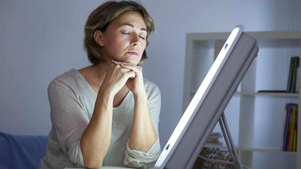 Mujer sentada junto a la lámpara de la terapia de luz para el trastorno afectivo estacional o la depresión
