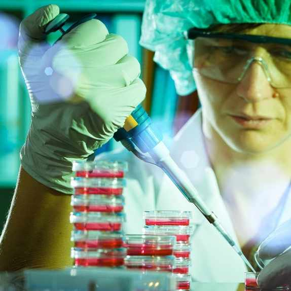 a close-up of a lab worker wearing gloves and protective gear, with lab equipment, doing research