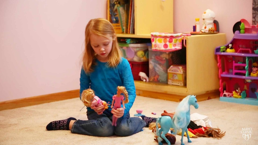 a little girl playing with Barbie dolls