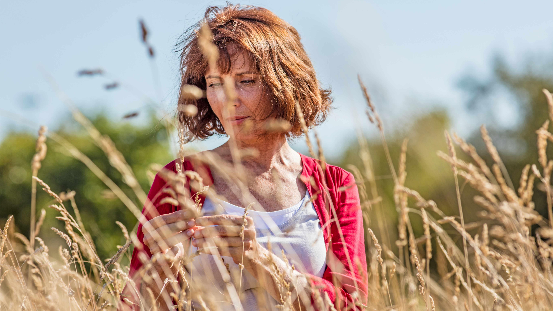 Mujer de mediana edad expuesta al exterior, con apariencia seria y pensativa