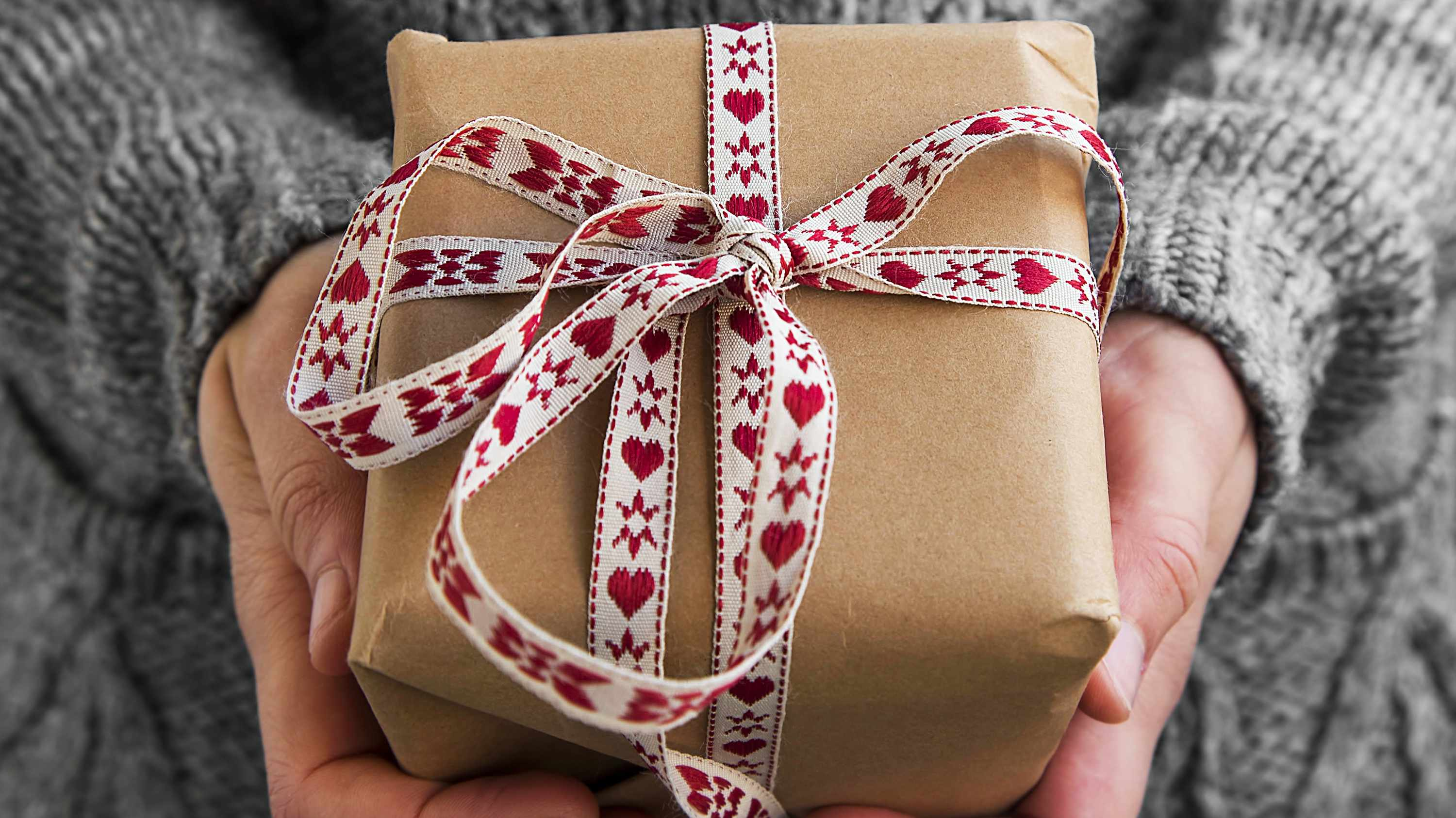 a person holding a present wrapped in brown gift paper with a heart ribbon
