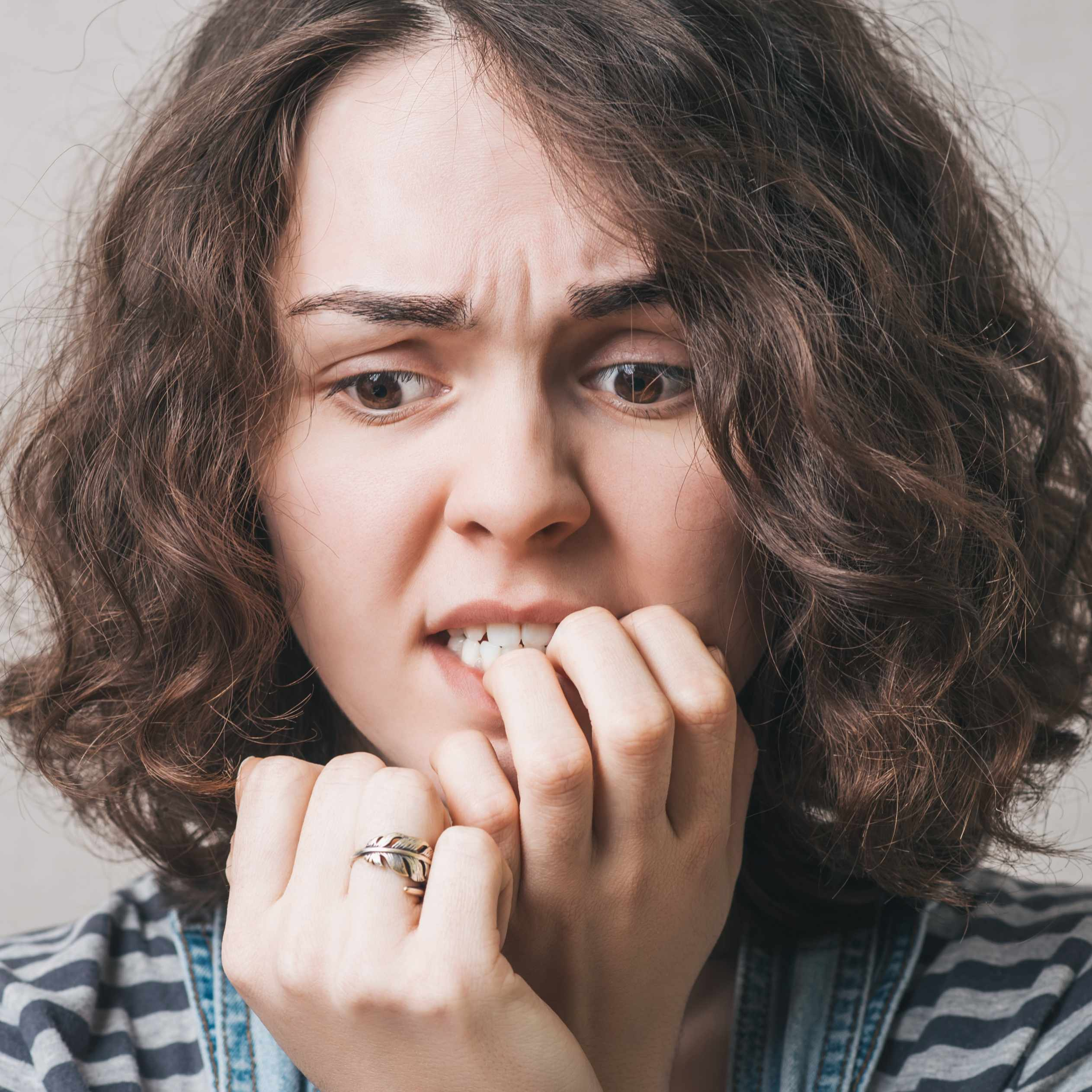 an anxious or nervous woman biting her nails and looking worried