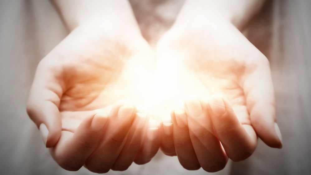 La luz brilla entre unas manos colocadas en forma de copa
