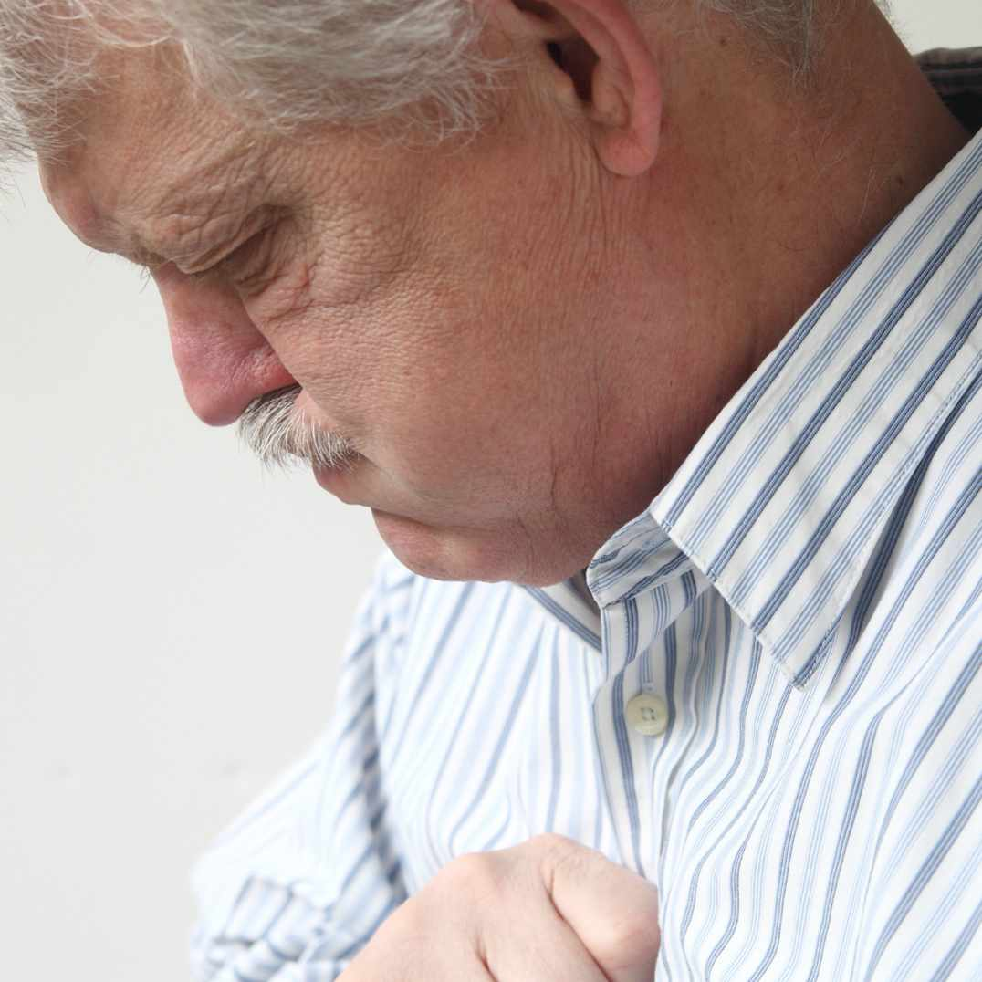 man holding chest with heartburn