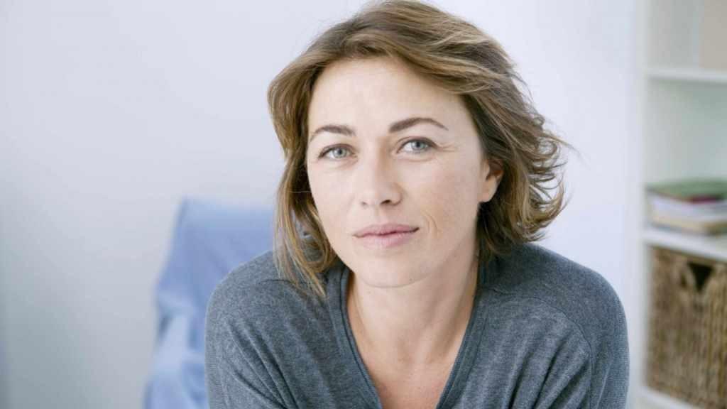 Mujer de mediana edad que luce relajada, pensativa, tranquila y meditativa