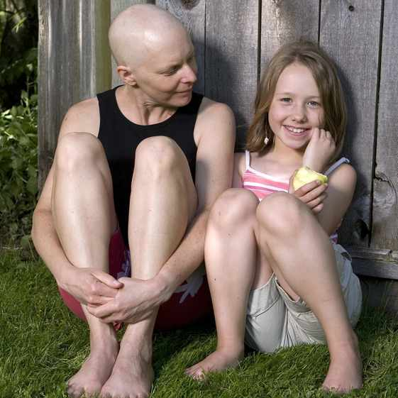 mother fighting breast cancer with her young daughter sitting outside leaning against a wooden fence