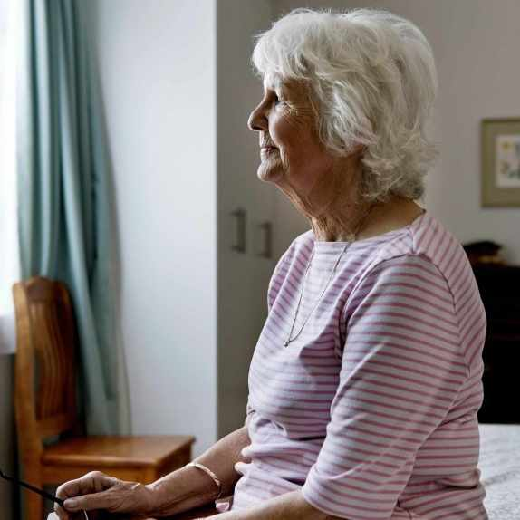 older woman sitting alone on a bed and thinking