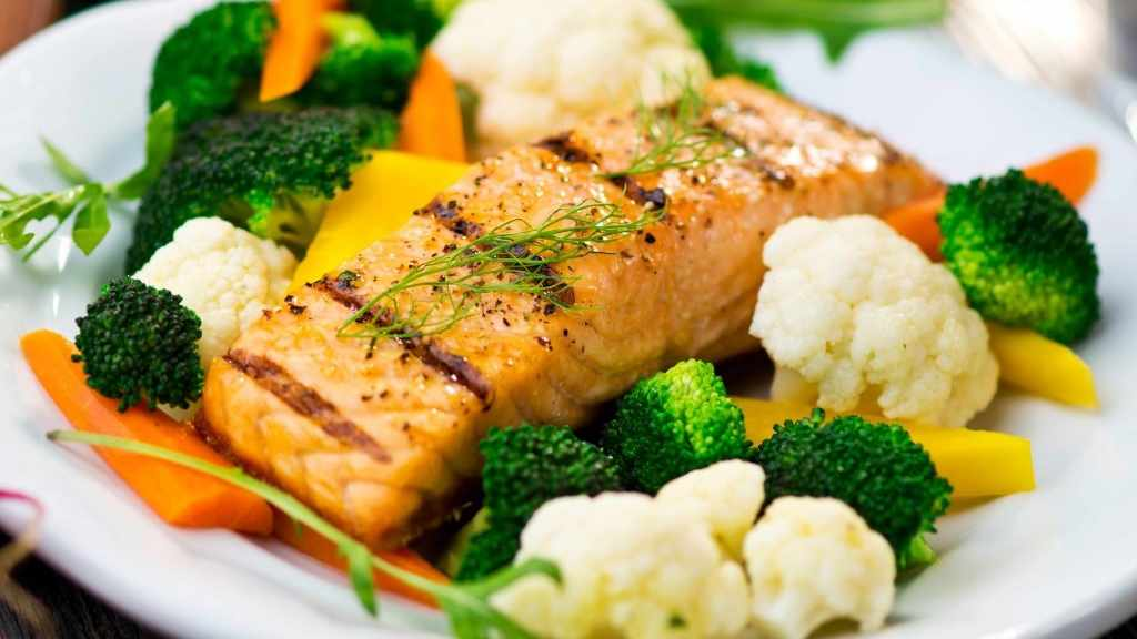a salmon fillet with cooked vegetables