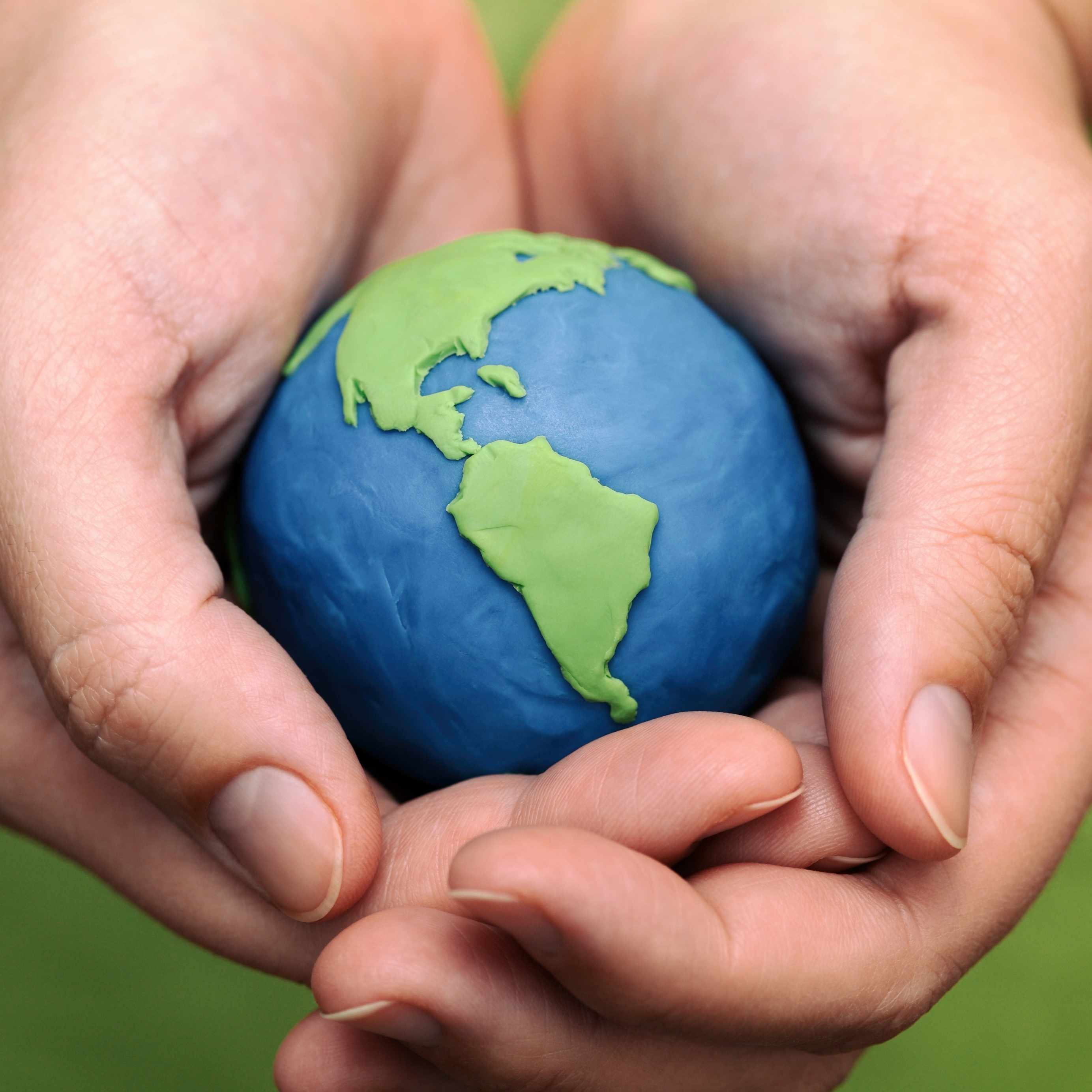 two hands holding a clay model of the earth, the world, a globe