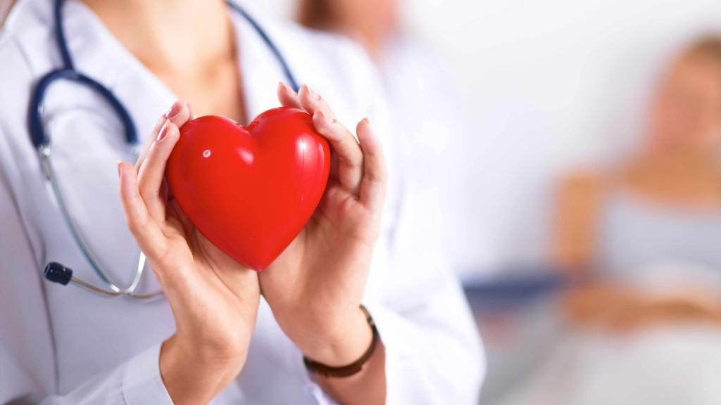 Una doctora con un estetoscopio en los hombros sostiene un corazón