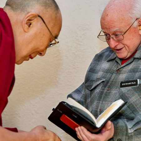 Dr. Joe Sharp holding a book and being greeted by the Dalai Lama