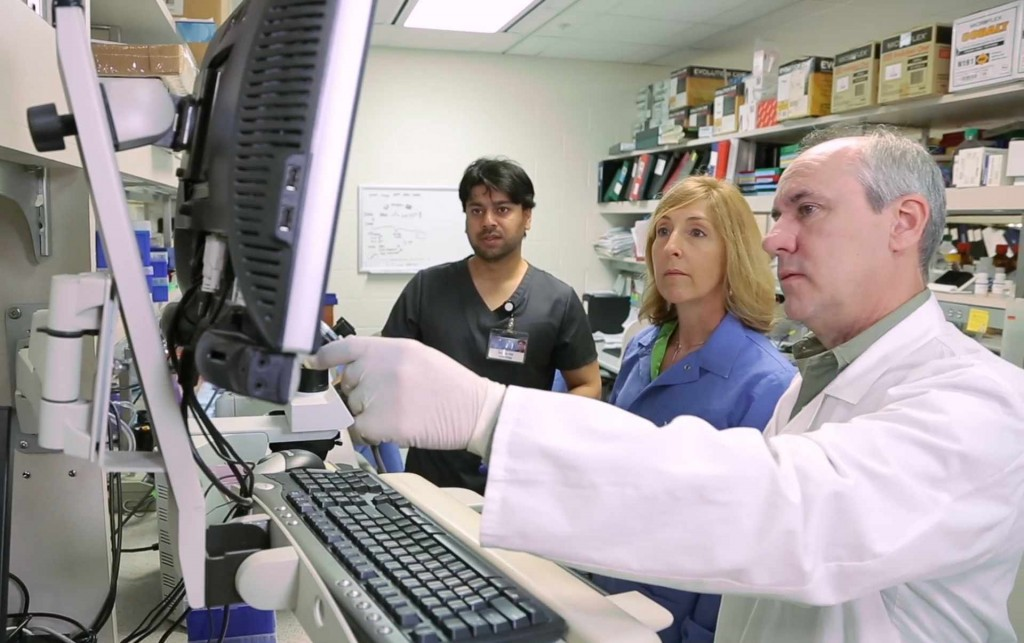 three doctors pointing and viewing a computer monitor in a cancer research lab