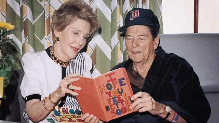 Pres. and Mrs. Ronald Reagan in Mayo hospital room looking at greeting cards