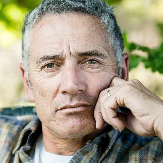 a middle-aged man with light gray hair looking serious and thoughtful