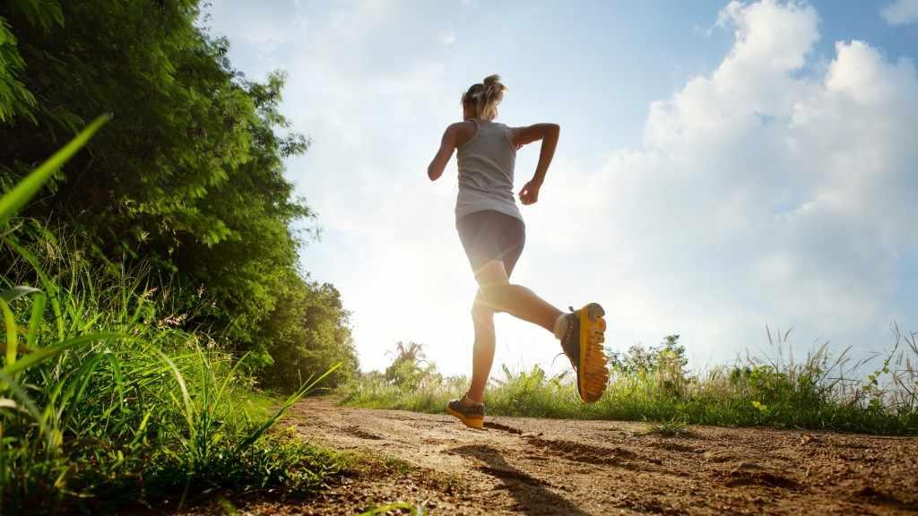 Una mujer corre por un camino en un día soleado
