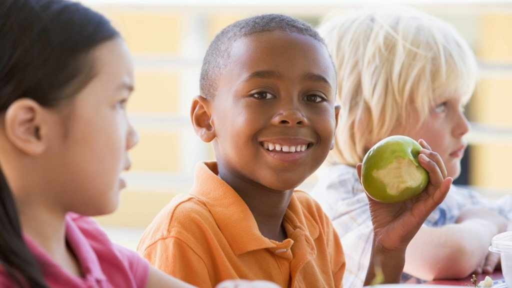 children at school lunch table, African-America boy eating an apple