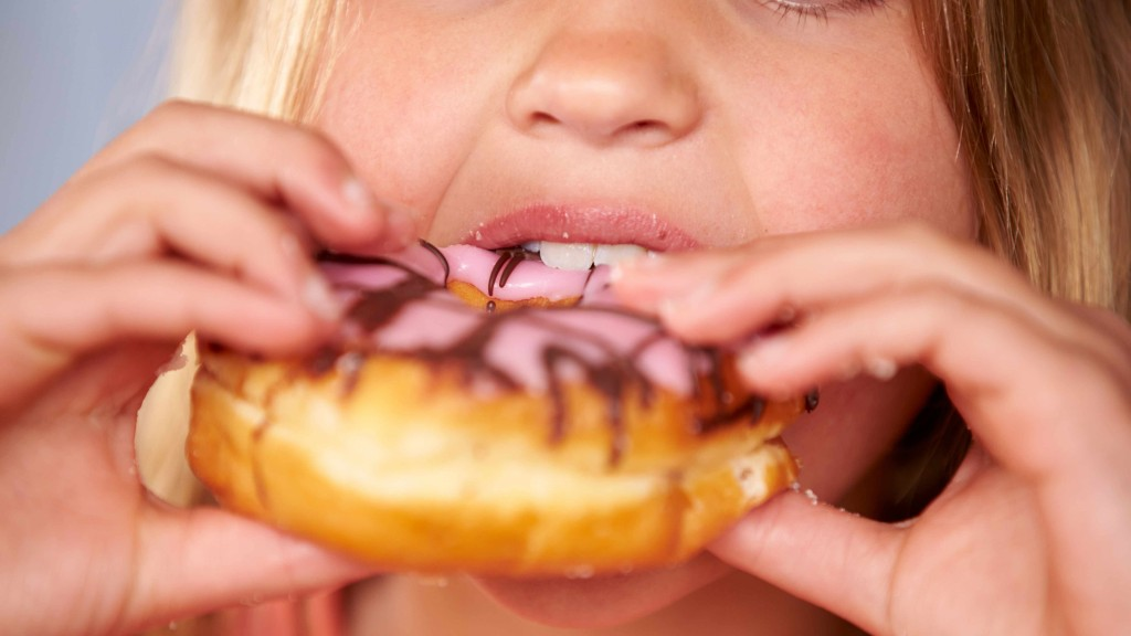 a young girl is eating a donut