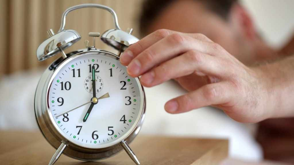 man waking up from sleep and turning off alarm clock 16x9
