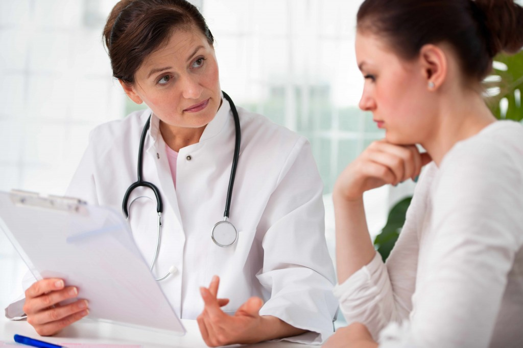 a woman in a doctor's office meeting with physician