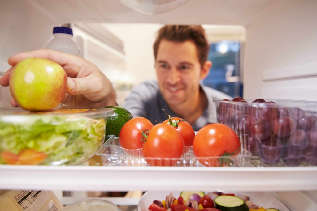 a man opening a refrigerator door with fruits and vegetables on the shelf
