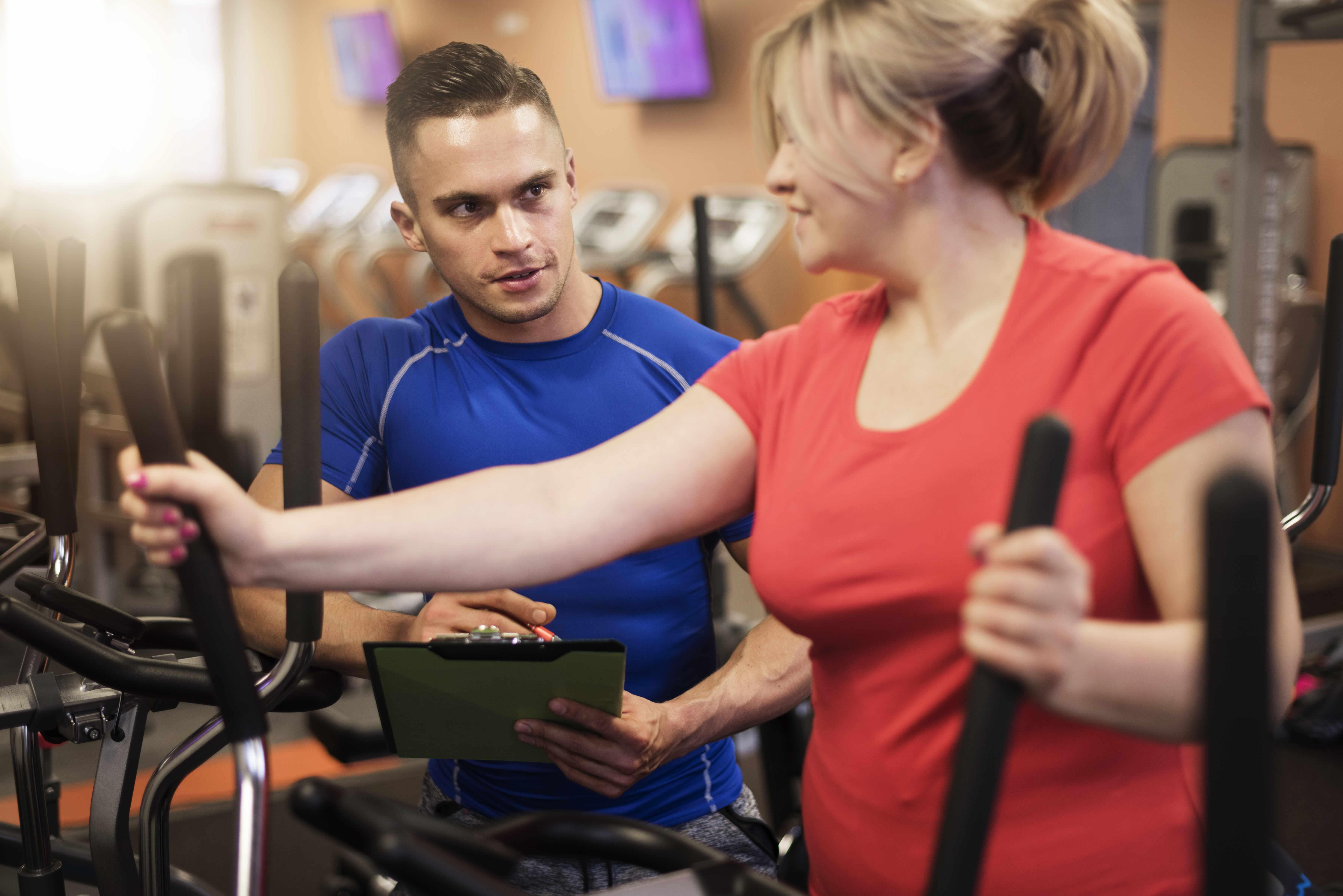 Una mujer hace ejercicio en la cinta de andar en un gimnasio y con un instructor
