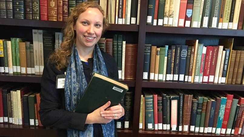 heart transplant patient Tara Brigham surrounded by library bookshelves