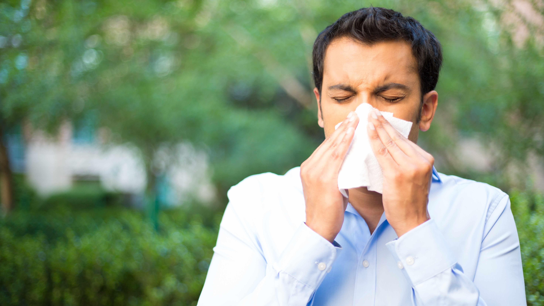 Un hombre se suena la nariz porque sufre de alergias y está afuera