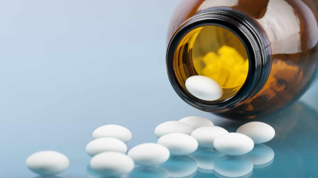 Un frasco de pastillas puesto de lado y con las tabletas regadas