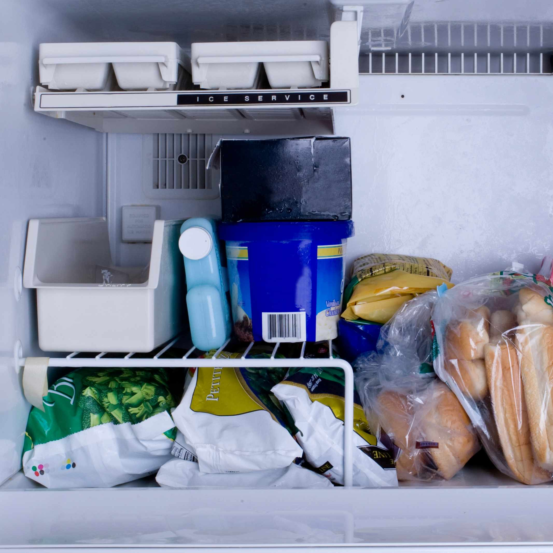a refrigerator freezer with vegetables, packages of meat and ice cube trays
