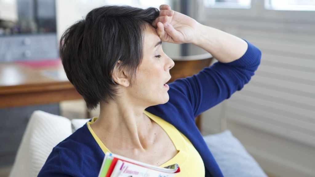 Una mujer se lleva la mano a la frente porque sufre un sofoco causado por la menopausia.